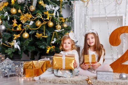 girls sitting next to Christmas tree